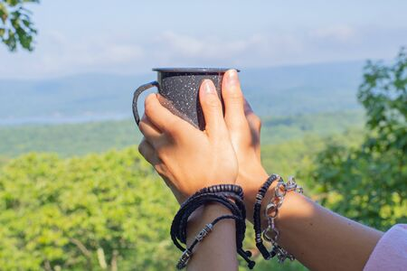 Hands with a mug on the background of a mountain landscape. Womans is holding cup of tea the outdoors.
