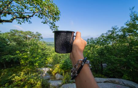Hand with a mug on the background of a mountain landscape. Womans is holding cup of tea the outdoors.