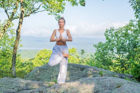 Young woman practicing yoga outdoors harmony with nature. Girl doing yoga standing in tree pose in morning on stone