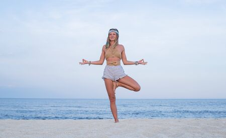 Young woman practicing yoga on the beach. Vrksasana pose and meditation