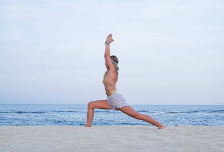 Young woman practicing yoga on the beach. Virabhadrasana I pose and meditation