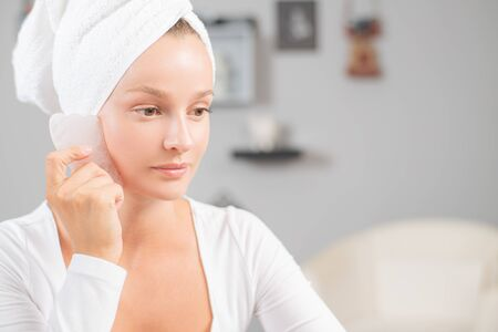 Face massage. Beautiful woman is getting massage face using jade stone for skin care, beauty treatment at home