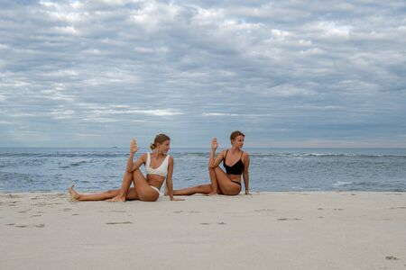 Yoga class. Young women practicing yoga on the beach. Stock Photo