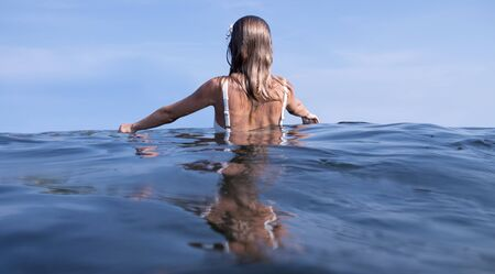 Relaxing on beach resort. Young beautiful woman enjoying seascape, standing in the water. Banco de Imagens - 130065078