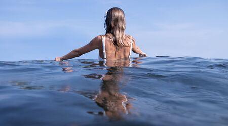 Relaxing on beach resort. Young beautiful woman enjoying seascape, standing in the water.