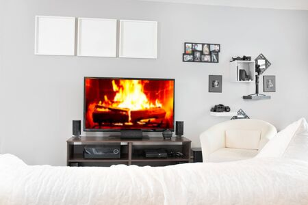 Cozy interior of living room with television on stand. Fireplace on television screen
