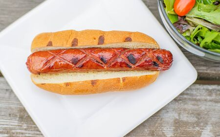 Hot dog on white plate. Fried sausage in bread.