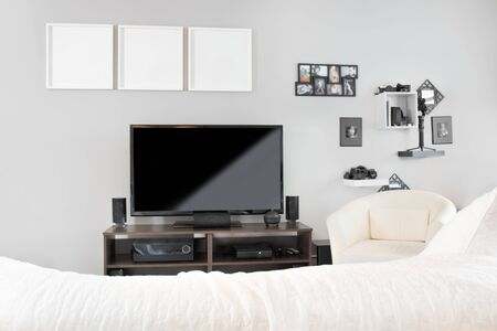 Cozy interior of living room with TV on stand. Blank black television screen