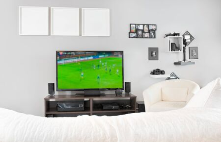 Cozy interior of living room with television, TV watching football, soccer match on television at home