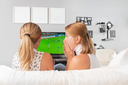 Happy friends or football fans watching soccer on tv and celebrating victory sitting on couch at home.