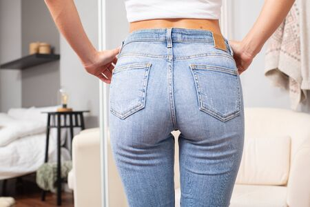 Woman wearing of jeans pants. Female bottom in tight jeans