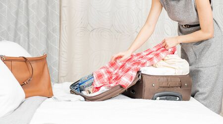 Beautiful woman packing suitcase in bedroom getting ready for road trip. Travel concept