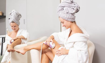 Laser depilation. Woman removing hair on her legs at home. Body Care.