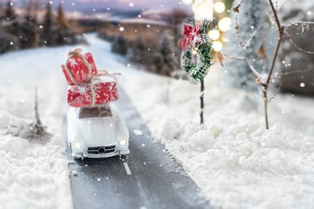 Miniature classic car carrying a christmas gifts on snowy winter landscape Zdjęcie Seryjne