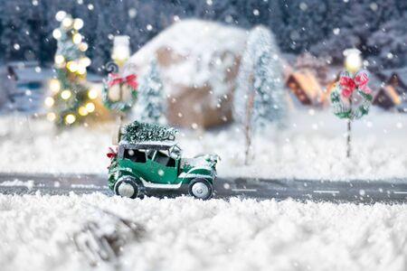Auto classica in miniatura che trasporta un albero di natale su una strada innevata su sfondo invernale Archivio Fotografico