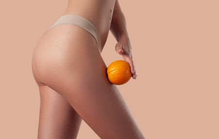 Skin care and anti cellulite massage. Perfect female buttocks without cellulite in panties. Beautiful woman's butt in underwear. Slim fit woman body with orange.