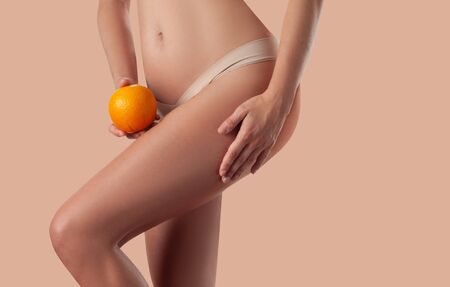 Slim woman is holding orange. Perfect female body without cellulite. Beautiful woman's hips in underwear. Skin care and anti cellulite massage