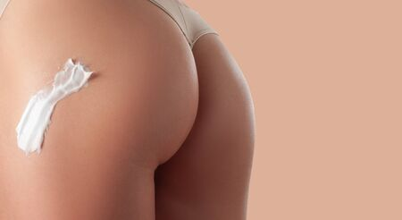 Body care. Woman applying cream on legs and buttocks. Female applying anti cellulite cream