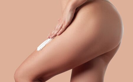 Body care. Woman applying cream on legs. Female applying anti cellulite cream