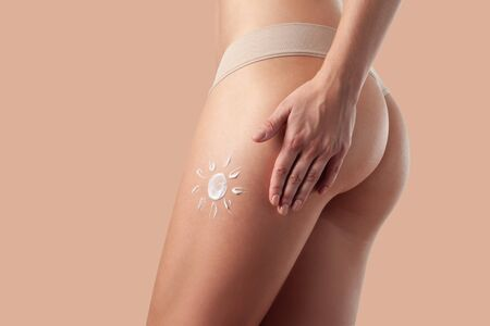 Body care and protection. Woman applying sunscreen lotion on legs and buttocks.