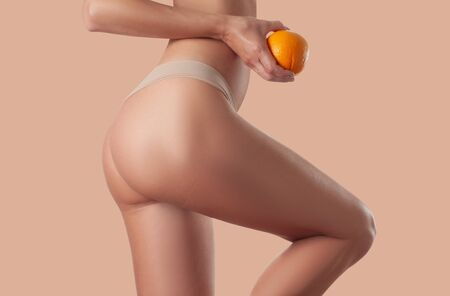 Slim woman is holding orange. Perfect female buttocks without cellulite. Beautiful womans butt in underwear. Body care and anti cellulite massage