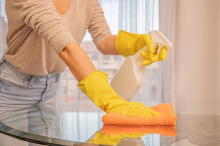 Woman in yellow gloves cleaning glass table. Spraying and wiping glass table. Zdjęcie Seryjne