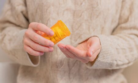 Woman takes pills vitamins. Woman is holding a jar of pills her hands