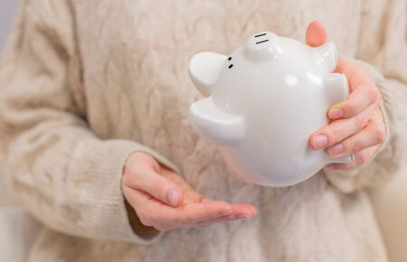 Woman is shaking piggy bank. Financial problem concept