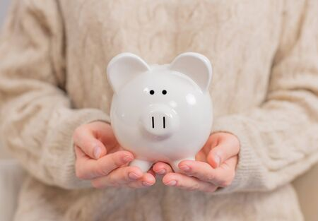 Woman is holding piggy bank in her hands. Woman makes savings puts money in a piggy bank.