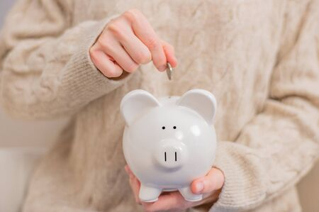 Woman makes savings puts money in a piggy bank. Woman is putting coins into piggy bank.