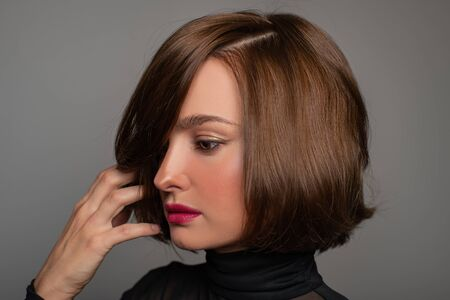 Brunette girl with shiny brown hair. Beautiful woman with bob haircut