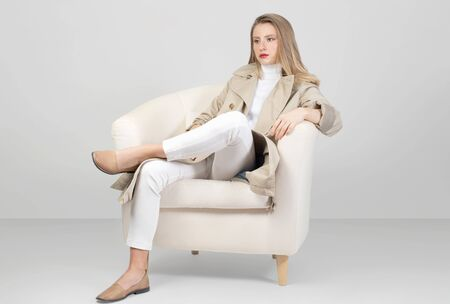 Fashionable clothes. Beautiful fashion woman in trench coat and pant in studio