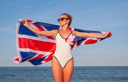 National Flag of United kingdom. Beautiful patriotic woman holding british flag on the beach. Imagens