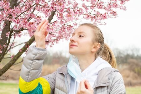 Beginning of Spring. Beautiful woman enjoying nature blooming tree. Spring allergy concept