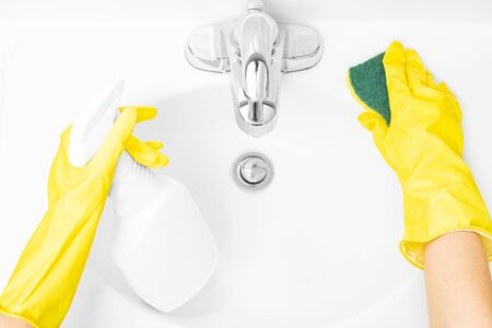 Woman in yellow rubber gloves is cleaning bathroom sink with detergent and sponge