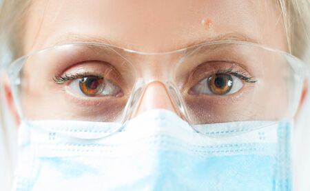 Close-up doctor's eyes with protective glasses and medical mask. Outbreaking Coronavirus