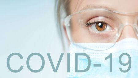 Coronavirus. Young specialist doctor in protective mask and eyeglasses, looking at camera. Outbreaking COVID-19 virus.