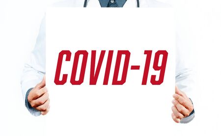 Concept of coronavirus quarantine. Novel coronavirus 2019-nCoV. Doctor with paper with the word Covid-19.