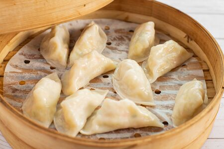 Traditional Korean dumplings in a traditional bamboo steamer. Top view.