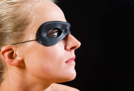 Blond girl wearing a mask, seen in profile against black background photo