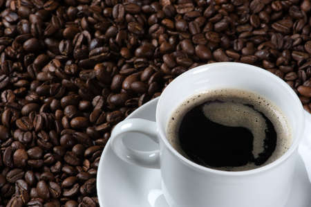 Closeup of a cup of fresh coffee, served on a plate covered with freshly roasted coffee beans Stock Photo