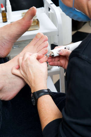 Foot therapist working om adult male feet, fixing the nails and skin.  Stock Photo