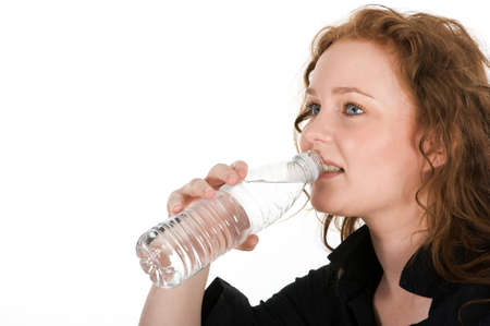 Young woman drinking mineral water directly from the bottle, isolated on white background
