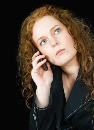 Beautiful girl with red hair speaking in mobile phone, seen against black background Stock Photo