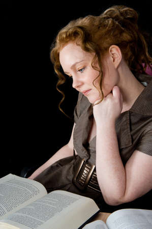 Beautiful girl with red hair reading a book photo