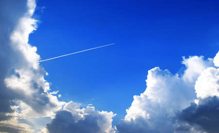 stratosphere: The jet plane in a stratosphere, reserves an equal white loop, the bright blue sky, the low cumulus clouds illuminated by the evening sun. Stock Photo