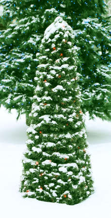 Little artificial fir-tree in to snow, decorated the garland of red bulbs on a background a large fir-tree with dark blue flashlights. photo