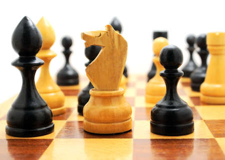 Wooden figures on a chess-board. Age-old intellectual game. photo