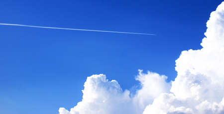 swelled: A service reactive airplane is in a stratosphere. Bright blue sky, large white cumuli.