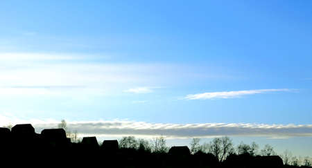 Black silhouettes of rural houses on a background winter sky. A long dark cloud is underlined by horizon.  photo